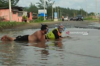 Berenang di jalan rusak. (Antara)